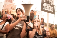 Photo of a Jobs with Justice protest with two young people in the front holding a megaphone.