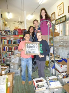 "Five people holding a ""Books Through Bars"" sign in front of a bookshelf."