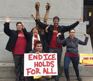"Five activists holding an ""End ICE Hold For All"" sign."
