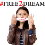 "A photo from the #Free2Dream campaign of Gisela Hernandez holding a ""Teacher"" banner"