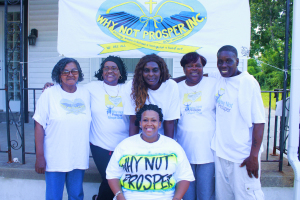 Members of Why Not Prosper in front of a banner.
