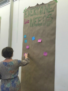 "Large poster with post-it notes below the heading ""Everyone has Needs"""
