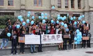 "Photo from Student Labor Action Project protest with light blue balloons, a large check, and a banner that reads ""SLAP""."