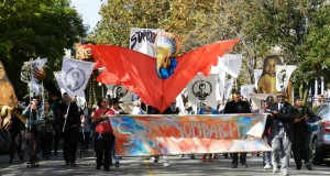 "Photo from Spiral Q's Peoplehood Parade with a banner that reads ""Soar in Solidarity"" on a colorful background and a large puppet of a bird."