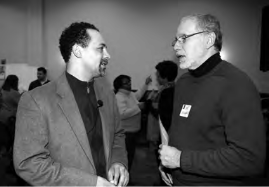 Bread & Roses board member Chris Rabb (left) speaks with attendee after moderating a panel. Photo: Harvey Finkle