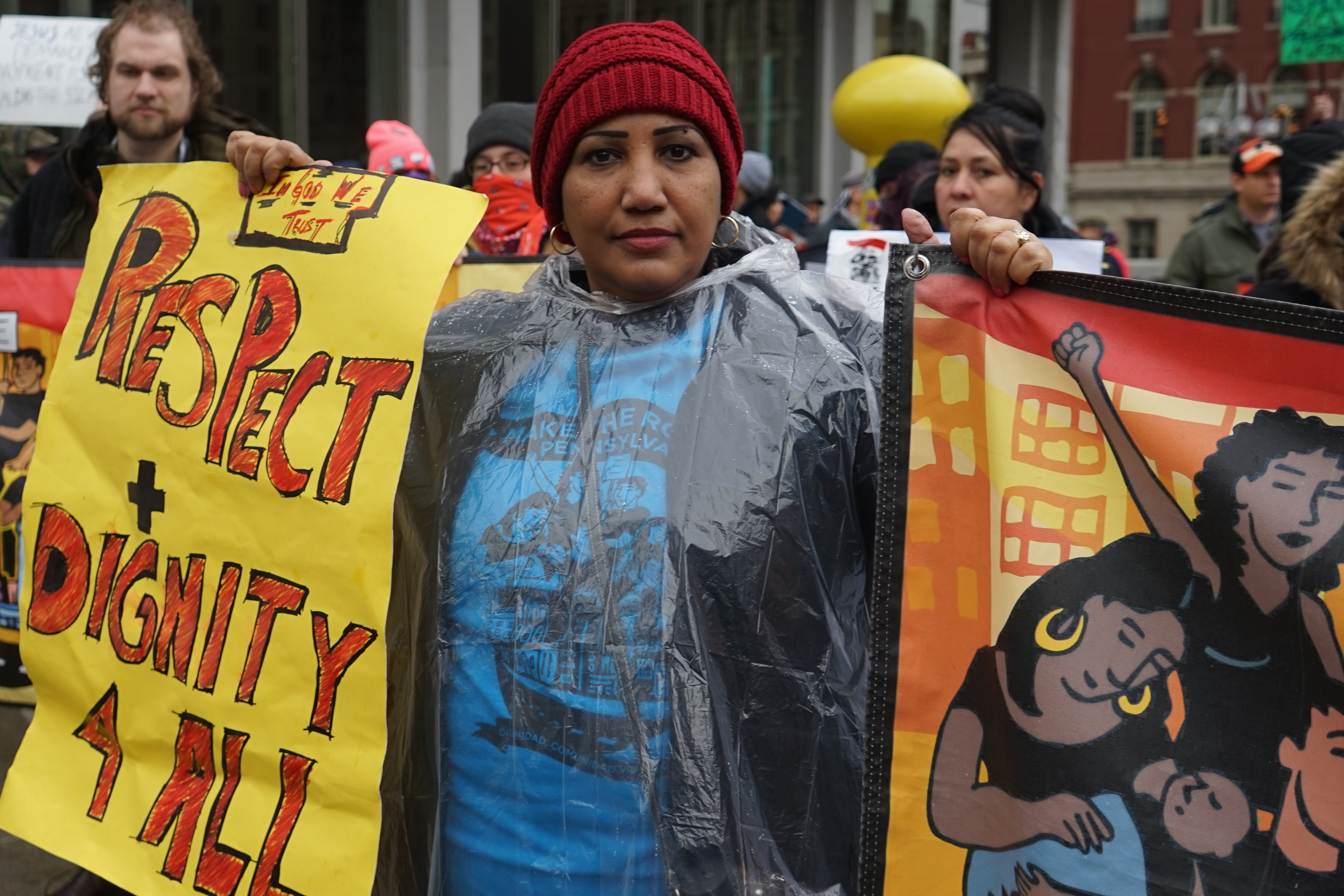 """Women holding sign that says """"Respect and Dignity for All"""""""