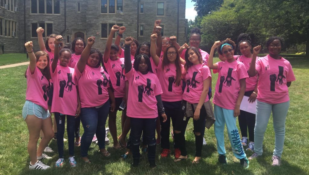 Girls and young women from Girls Justice League raise their fists