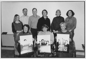 photo of Jobs with Justice members holding Jobs with Justice posters