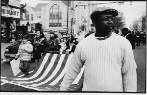 Photo of Henry Nicholas at a protest carrying an American flag