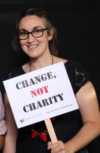 """Photo of Leah Pillsbury holding a sign that read """"Change, Not Charity"""""""