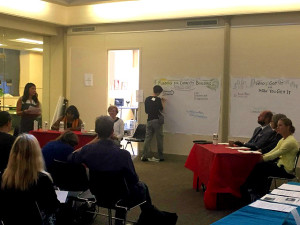 A person taking notes on a panel discussion at the front of the room.
