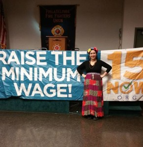"A person standing in front of a large banner that reads ""Raise the Minimum Wage! 15NOW.org"""