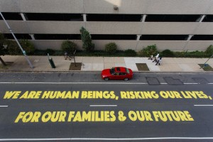 """A street mural that reads """"We are human beings, risking our lives, for our families & our future"""""""
