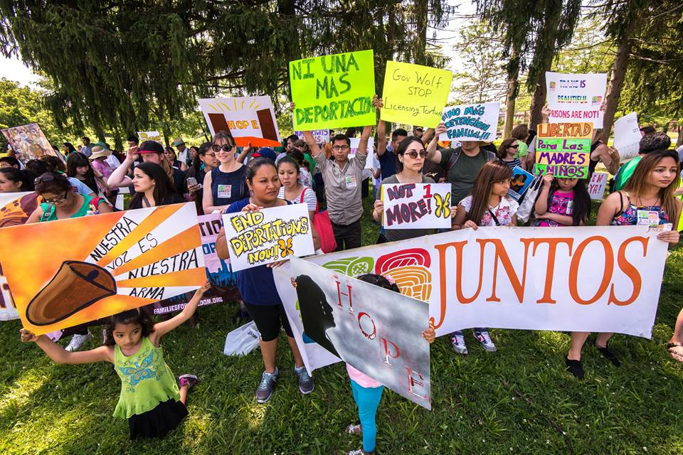 "JUNTOS members with signs reading ""JUNTOS"", ""Not 1 more!"", ""End Deportations Now!"", ""HOPE"", ""Nuestra Voz Es Nuestra Arma"", ""Ni Una Mas Deportacion"", ""Gov Wolf Stop Licensing Torture"", ""Trans is Beautiful Prisons are Not!"", and ""Libertad Para Las Madres y Nin@s"""