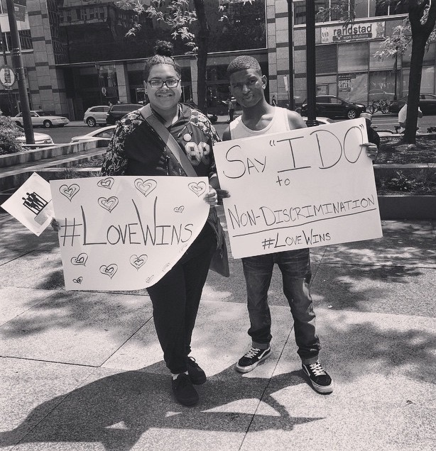 """Two young people holding up signs reading """"#LoveWins"""" and """"Say 'I DO' to Non-Discrimination"""""""