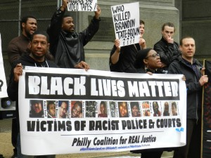 "Photo from Coalition for REAL Justice protest with a banner that reads ""Black Lives Matter""."