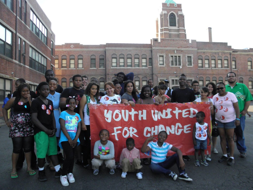 """Photo from Youth United for Change protest. Protesters gather around a large banner that reads """"Youth United for Change""""."""