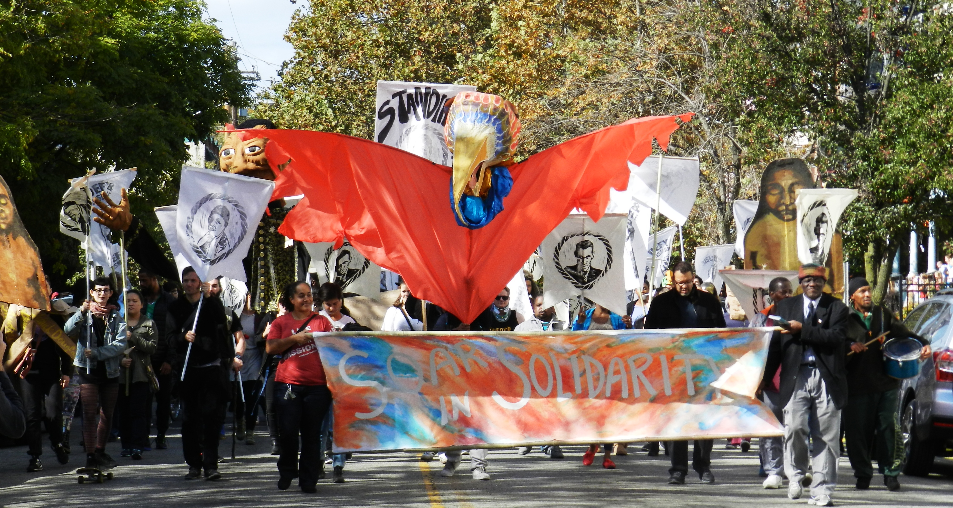 "Photo from Spiral Q's Peoplehood Parade. At the front is a banner that reads ""Soar in Solidarity"" on a colorful background and a large puppet of a bird."