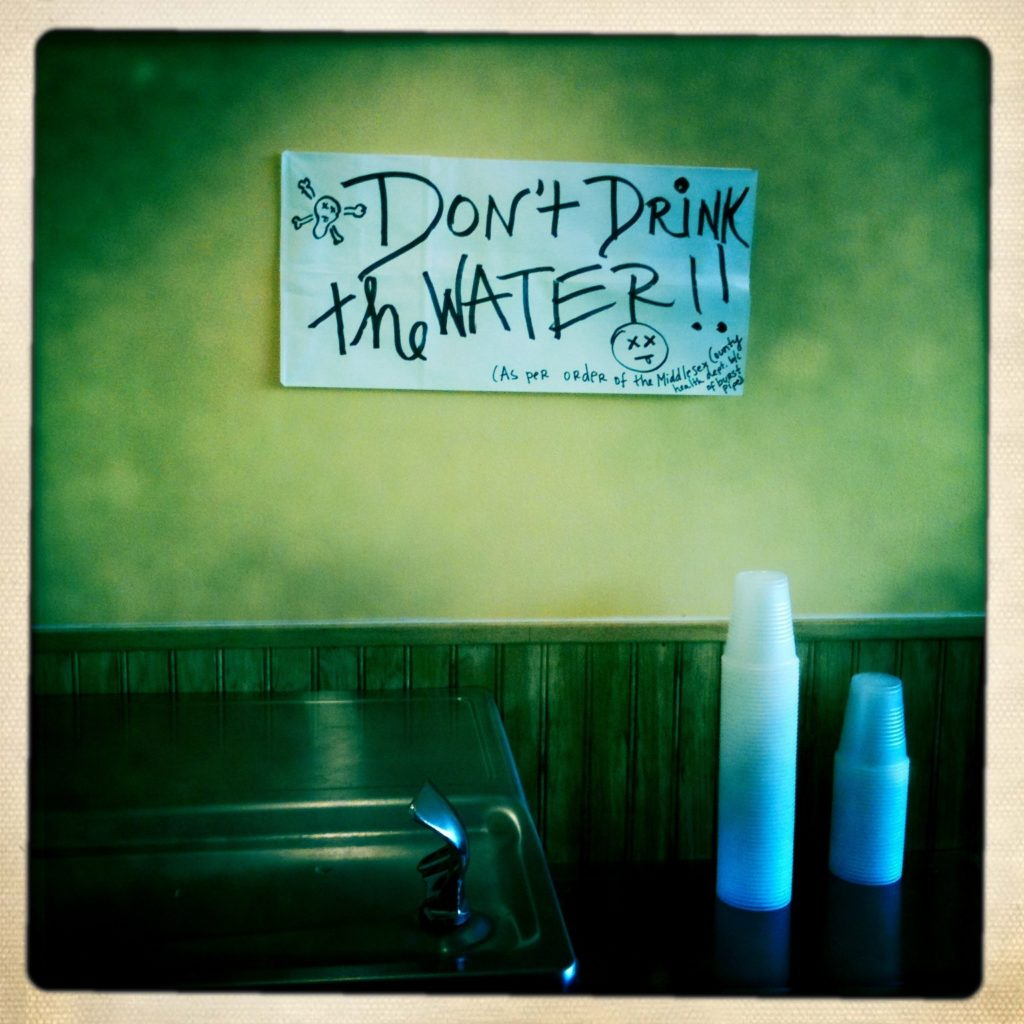 """Photo of a water fountain and a sign reading """"""""Don't Drink the Water!!"""