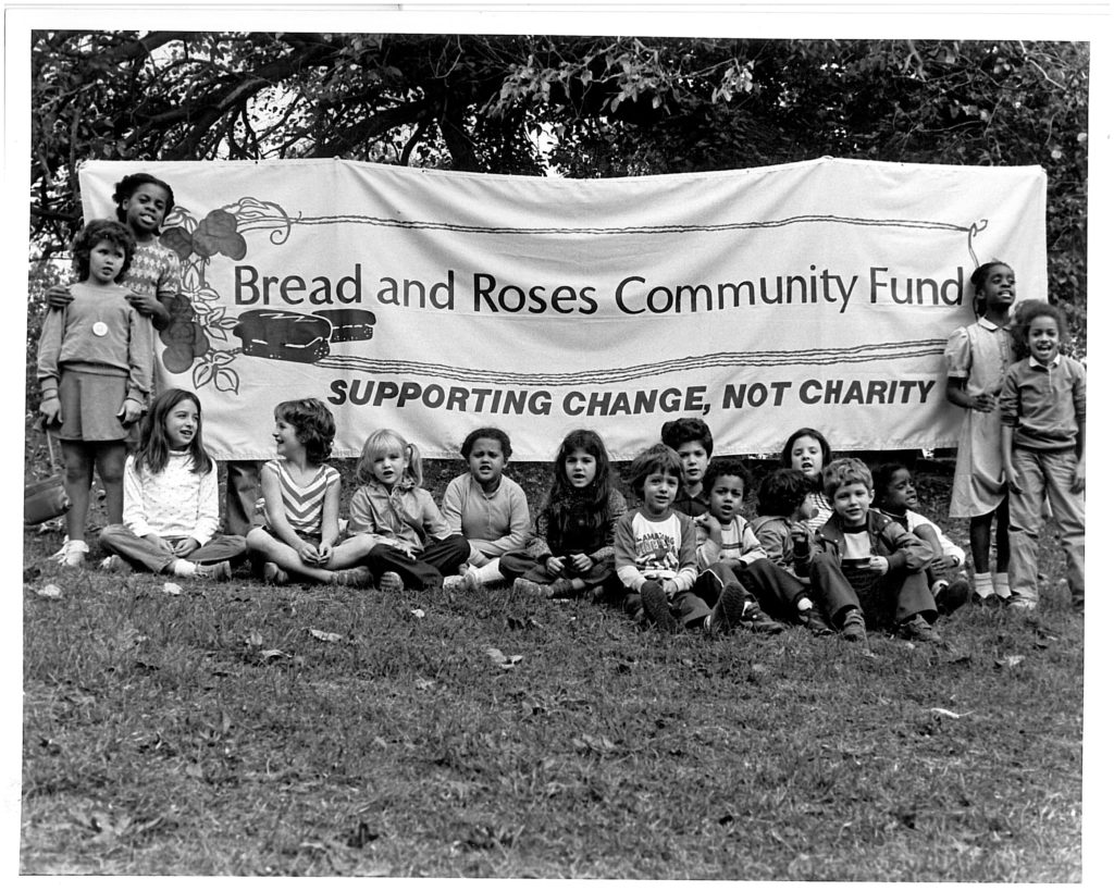 Children sitting in front of Bread & Roses Community Fund sign