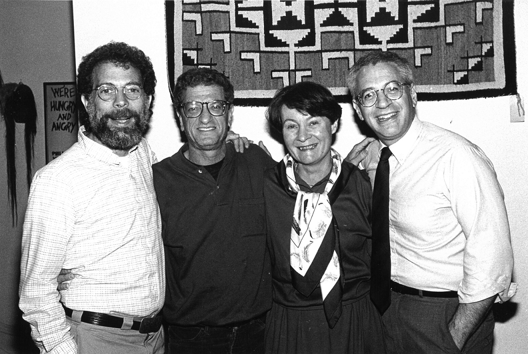 Black and white photo of four people standing and smiling
