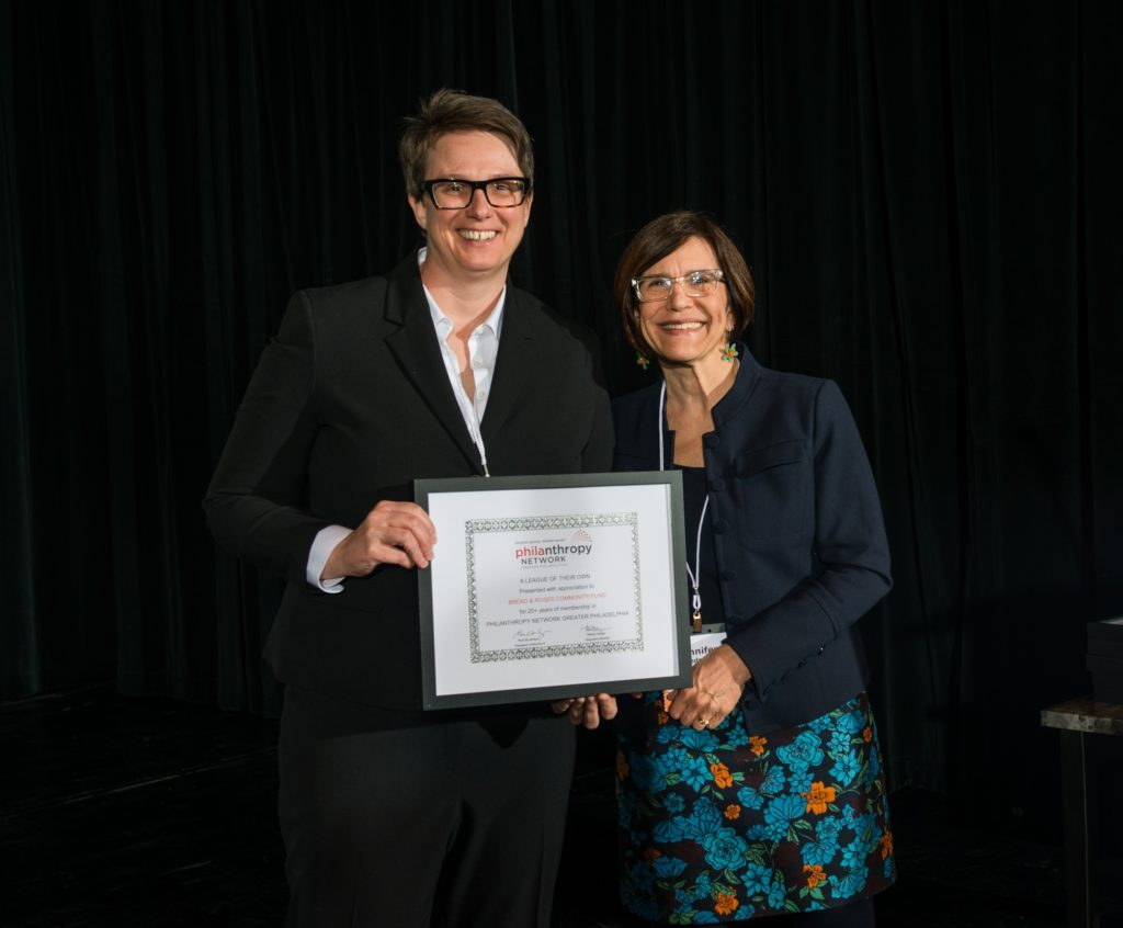 Two people standing facing the camera smiling holding a framed certificate