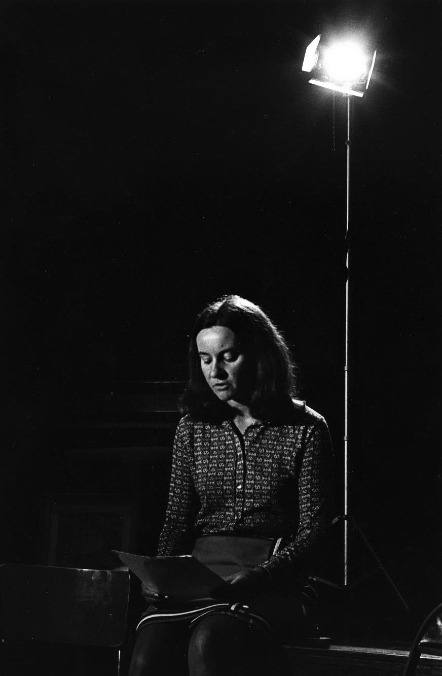 Person sitting in a dark room looking down at paper
